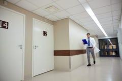 Lekarka z schowka odprowadzeniem wzdłuż szpitala Zdjęcia Stock