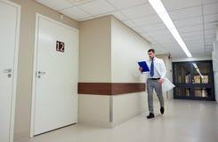 Lekarka z schowka odprowadzeniem wzdłuż szpitala Obrazy Royalty Free