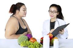 Lekarka z schowkiem i otyłym pacjentem Zdjęcie Stock