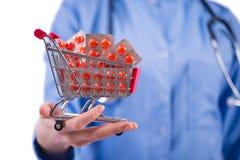 Lekarka z wózek na zakupy pełno pigułki na bielu Zdjęcie Royalty Free