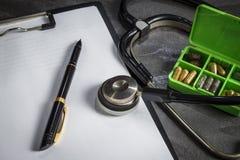 Lekarka zestaw: stetoskop, zbiornik z pigułkami i pióro z papką, fotografia stock