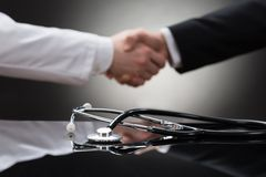 Lekarki i biznesmena chwiania ręka Obraz Stock