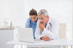 Lekarki patrzeje laptop obraz stock