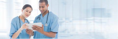 Lekarki patrzeje pastylkę przeciw błękitnemu tłu fotografia royalty free
