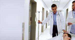 Lekarki pcha przeciwawaryjnego blejtramu łóżko w korytarzu zbiory wideo