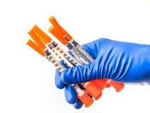 Lekarki ręka w błękitnej medycznej rękawiczce trzyma kilka strzykawki z medycznego rozwiązania białym odosobnionym tłem grypa zdjęcia royalty free
