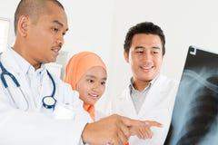 Lekarki sprawdza na promieniowanie rentgenowskie obrazie cyfrowym zdjęcia stock