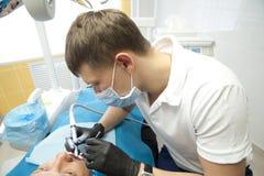 Lekarki stomatologiczny chirurgicznie dział wykonują stomatologiczną chirurgicznie operację zdjęcie royalty free