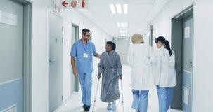 Lekarki w szpitalnym korytarzu przechodzą heathcare pracownika pomaga starszego pacjenta 4k zdjęcie wideo