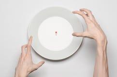 Lekarstwa i nieprzystojny odżywianie temat: ludzki ręka chwyt talerz z pigułkami odizolowywać na białego tła odgórnym widoku Obrazy Royalty Free