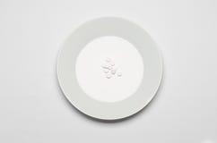 Lekarstwa i nieprzystojny odżywianie temat: ludzki ręka chwyt talerz z pigułkami odizolowywać na białego tła odgórnym widoku Zdjęcie Royalty Free