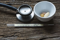 Lekarstwa w filiżance, termometrze i stetoskopie, Zdjęcia Stock