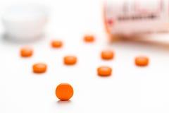 Lekarstwo, pigułki rozlewa out na białej powierzchni Fotografia Stock