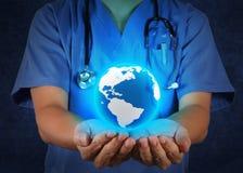 Lekarz Medycyny trzyma światową kulę ziemską w jego jak medyczną sieć ręki Obraz Stock
