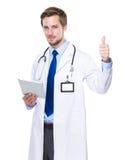 Lekarz medycyny z pastylką up i kciukiem Obraz Stock