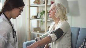 Lekarz odwiedza przechodzić na emeryturę kobiety i używa miarę nacisk zdjęcie wideo