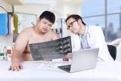 Lekarz pokazuje promieniowanie rentgenowskie z nadwagą osoba fotografia royalty free