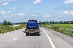 Lekka ciężarówka jest holowniczym ciężarówką który niesie błękit, uszkadzający, łamający samochód osobowy na autostradzie między  obrazy royalty free