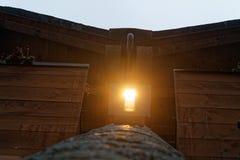 Lekka lampa pod drewnianym dachem z ciemnymi drewnianymi promieniami, Obraz Royalty Free