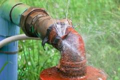 Lekken het de loodgieterswerk hoofdbuis en water, oude het staalroest van de kraanpijp op grasvloer Royalty-vrije Stock Afbeeldingen