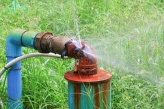 Lekken het de loodgieterswerk hoofdbuis en water, oude het staalroest van de kraanpijp op grasvloer Stock Foto
