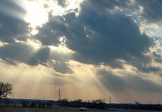 Lekki łamanie przez chmur nad autostradą z samochodami przy zmierzchem z elektrycznym góruje z fabryką w tle Obraz Royalty Free