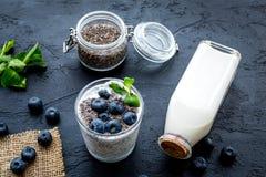 Lekki deser z ziarnami, jogurtem, czarną jagodą i mennicą chia, Czarny tło Fotografia Stock