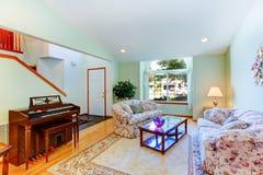 Lekki nowy żywy pokój z kwiecistym meble i pianinem Fotografia Stock