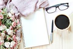 Lekmanna- eller bästa sikt för lägenhet av halsduken, öppet tomt anteckningsbokpapper, kaffekoppen och glasögon på träbakgrund Royaltyfri Fotografi