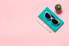Lekmanna- foto för idérik lägenhet av workspaceskrivbordet med akvamarinanteckningsboken, glasögon, bakgrund för rosa färger för  Arkivbild