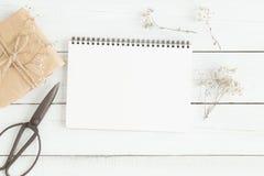 Lekmanna- foto för lägenhet av den tomma vita anteckningsboken på den wood tabellen fotografering för bildbyråer