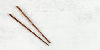Lekmanna- foto för lägenhet - par av mörka träpinnar på det vita brädet Brett baner för asiatisk/kinesisk mat, utrymme för text p arkivbilder