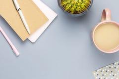 Lekmanna- inrikesdepartementetskrivbord för lägenhet Kvinnlig workspace med anmärkningsboken, glasögon, te rånar, dagboken, växt  royaltyfria foton