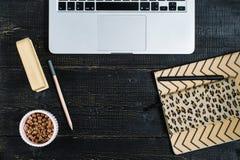 Lekmanna- inrikesdepartementetskrivbord f?r l?genhet Kvinnlig workspace med b?rbara datorn, guld- tillbeh?r, dagbok p? svart bakg arkivfoton
