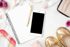 Lekmanna- inrikesdepartementetskrivbord f?r l?genhet Kvinnlig workspace med mobiltelefonen, pappersnotepaden, guld- skor och kvin royaltyfria foton