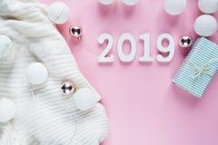 Lekmanna- julbegreppslägenhet Varma hemtrevliga vita vinterkläder, nummer 2019 och julpyntram på rosa färger royaltyfri fotografi