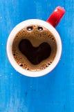 Lekmanna- kopp kaffe för lägenhet med hjärtaform ovanför blå träbakgrund fotografering för bildbyråer