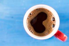 Lekmanna- kopp kaffe för lägenhet med hjärtaform ovanför blå träbakgrund royaltyfri fotografi
