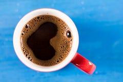 Lekmanna- kopp kaffe för lägenhet med hjärtaform ovanför blå träbakgrund arkivfoton