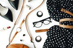 Lekmanna- kvinnlig kläder- och tillbehörcollage för lägenhet med den svarta klänningen, exponeringsglas, skor för hög häl, handvä Arkivfoton