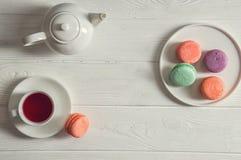 Lekmanna- lägenhet close upp Ljusa franska macarons för Provence frukost på en rund platta, en kopp av bärte, en tekanna kopiera  arkivfoto