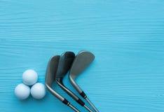 Lekmanna- lägenhet: Golfklubbar golfbollar på den blåa trätabellen arkivbilder