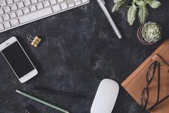 Lekmanna- lägenhet Mörk tabell för kontor med datornotepaden, mus, penna, p Arkivbild