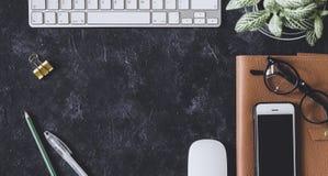 Lekmanna- lägenhet Mörk tabell för kontor med datornotepaden, mus, penna, p Arkivfoto