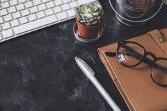 Lekmanna- lägenhet Mörk tabell för kontor med datornotepaden, mus, penna, p Royaltyfri Foto