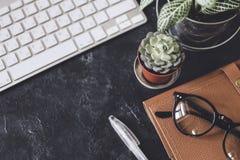 Lekmanna- lägenhet Mörk tabell för kontor med datornotepaden, mus, penna, p Fotografering för Bildbyråer