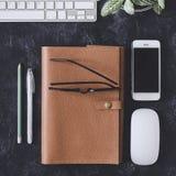 Lekmanna- lägenhet Mörk tabell för kontor med datornotepaden, mus, penna, p Royaltyfri Bild