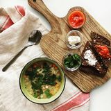 Lekmanna- matstilleben för lägenhet av ljusa mellanmål av bröd, tomaten, korvar och koppen av soppa Royaltyfria Foton
