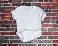 Lekmanna- modell för lägenhet av den vita utslagsplatsskjortan på tegelstenbakgrund arkivbild