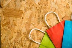 Lekmanna- pappers- shoppingpåse för lägenhet på en träbakgrund royaltyfri bild